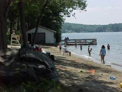 View along sandy Beach with people sitting along shore on left awith water to their right, small building with dock in mid-ground at end of bsandy beach,forest bounding lake is in background